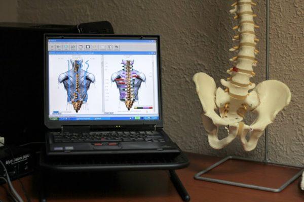 Genesis Chiropractic Clinic Horsham PA back adjustment spine pelvic skeleton model laptop display